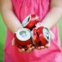 Girl holding 3 crushed aluminium cans